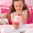 Foto Stock: Smiling girl saving money in piggybank