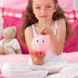 Stock Photo: Little girl saving money in a piggybank