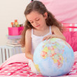 Stock Photo: Little girl having fun with a terrestrial globe