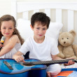 Brother and sister playing in the bedroom — Stock Photo