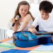 Brother and sister having fun with a guitar — Stock Photo