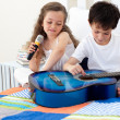Brother and sister having fun with a guitar — Stock Photo #10295357