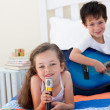 Stock Photo: Close-up of cute girl girl singing and her brother playing gui