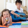 Little boy playing guitar and his sister singing — Stok fotoğraf