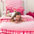 Little girl writing on bed — Stock Photo