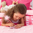 Close-up of a Little girl writing on bed — Stock Photo