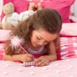 Close-up of a Little girl writing on bed — Stock Photo #10295382