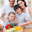 Portrait of happy parents cooking with their children — Stock Photo