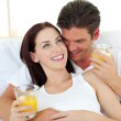 Young couple drinking orange juice lying on their bed - Stok fotoraf