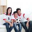 Jolly young family watching a football match — Stok fotoğraf