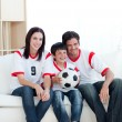 Stock Photo: Jolly young family watching a football match