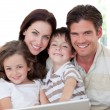 Smiling family using a laptop — Stock Photo