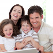 Smiling family using a laptop in the living-room — Stock Photo