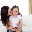 Attentive mother kissing her little girl — Stock Photo #10295470
