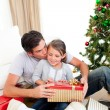 Father kissing his little daughter after giving her a Christmas — Foto de Stock
