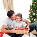 far kysser hans lilla dotter efter att ge henne en jul — Stockfoto