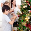 Happy children and parents decorating a Christmas tree - Stock Photo