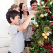 Happy family decorating a Christmas tree with boubles - Stock Photo