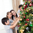 Happy family decorating a Christmas tree with boubles — Stock Photo #10295511