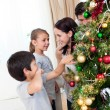 Smiling family decorating a Christmas tree with boubles - Stock Photo