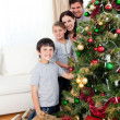Happy family decorating a Christmas tree with boubles and presen — Stock Photo