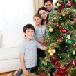 Happy family decorating a Christmas tree with boubles and presen - Stock Photo