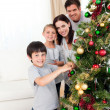 Smiling family decorating a Christmas tree - Stock Photo