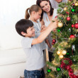 Happy family decorating a Christmas tree with boubles — Stock Photo #10295516