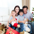 Happy family at Christmas time holding lots of presents — Stock Photo