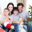 Stock Photo: Portrait of a smiling family at Christmas time holding lots of p