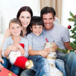 Stock Photo: Portrait of smiling family at Christmas time holding lots of p
