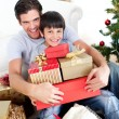 Happy father and son holding Christmas presents - Stok fotoğraf