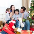 Happy family playing with Christmas gifts — Stock Photo