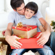 Father kissing his son after giving him a Christmas gift — Stock Photo