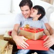 Son kissing his father after receiving a Christmas gift - Stock Photo
