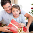 Portrait of a surprised little girl holding a Christmas present — Stock Photo #10295532