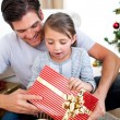 Surprised little girl holding a Christmas present with her fathe — Stock Photo