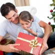 Stock Photo: Surprised little daughter opening a Christmas present with her f