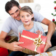 Happy little girl with her father receiving a Christmas present — Stockfoto