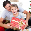 Surprised little girl opening a Christmas present with her fathe — Stockfoto