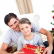 Smiling little girl with her father holding a Christmas gift — Stock Photo