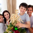 Happy little boy decorating a Christmas tree with his family — Stock Photo