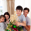 Smiling family decorating a Christmas tree at home — Stock Photo