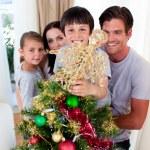 Happy family decorating a Christmas tree — Stock Photo