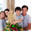 Happy little kid decorating a Christmas tree with his family - Stock Photo
