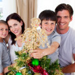 Portrait of a family decorating a Christmas tree - Stock Photo