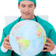 Charming doctor holding terrestrial globe — Stock Photo