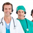 Smiling medical team using headsets — Stock Photo