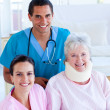 Two smiling doctors taking care of an injured senior woman — Stock Photo