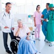 Positive medical team taking care of a senior woman — Stock Photo #10295995